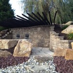Custom stonework in garden with long wooden stakes