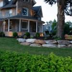 Home with large stones around flower garden