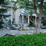 Stone house with stone hardscaping elements and pond